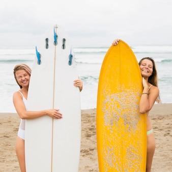 Vista frontale di amiche in spiaggia in posa con tavole da surf