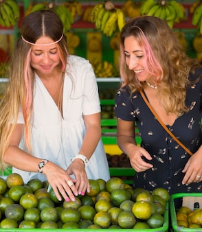 Front view of female friends at the farmers market picking limes