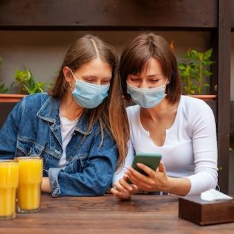 Vista frontale di amici di sesso femminile guardando smartphone pur avendo un po 'di succo