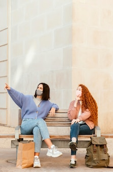 Front view of female friends with face masks outdoors sitting on a bench with copy space