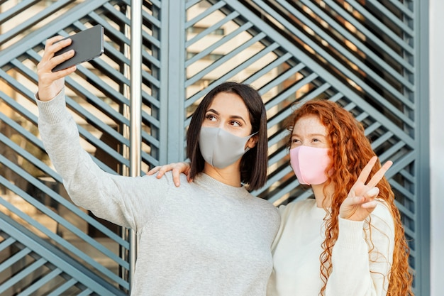 Front view of female friends with face masks outdoors taking a selfie