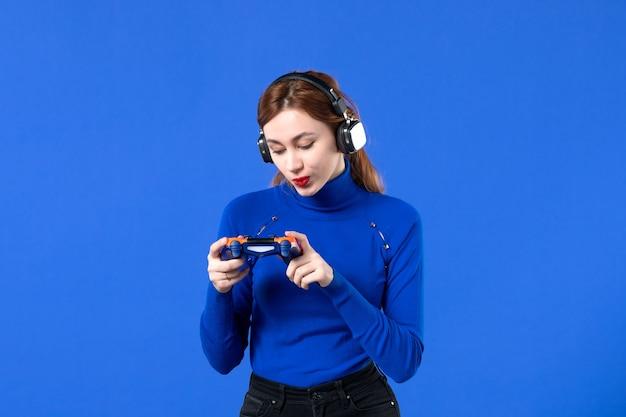 Вид спереди женщина-геймер с наушниками и геймпадом на синем фоне молодежное видео диван молодая выигрышная виртуальная девушка взрослый игрок радость