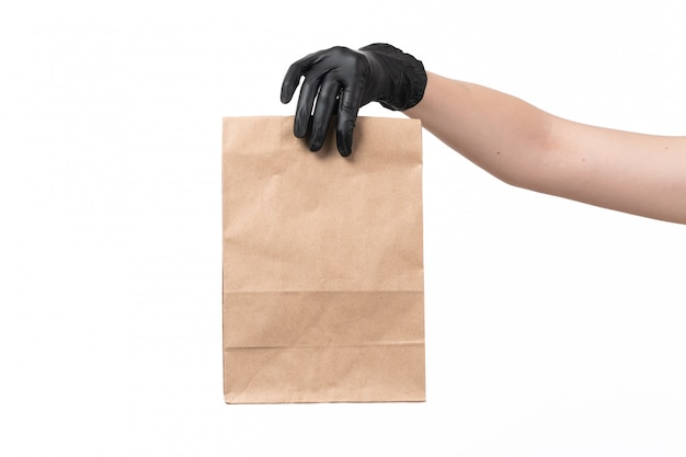 A front view female hand in black glove holding paper package on white