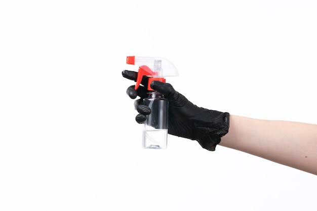 A front view female hand in black glove holding spray on white