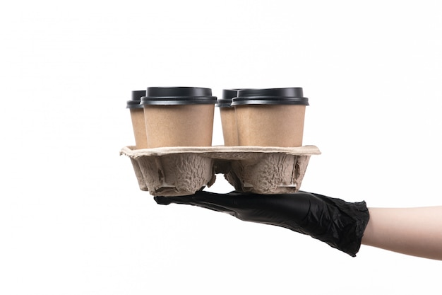 A front view female hand in black gloves holding cups with coffee on white job