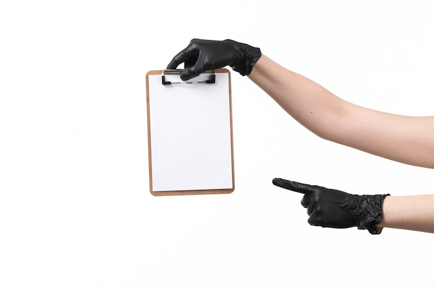 A front view female hand in black gloves holding notepad on white job