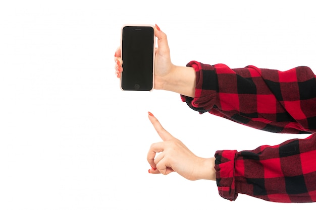 A front view female hand in black-red checkered shirt holding smartphone showing warning sign on the white