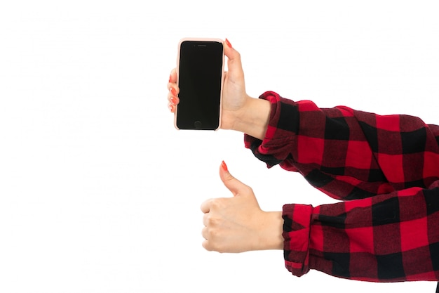 A front view female hand in black-red checkered shirt holding smartphone on the white