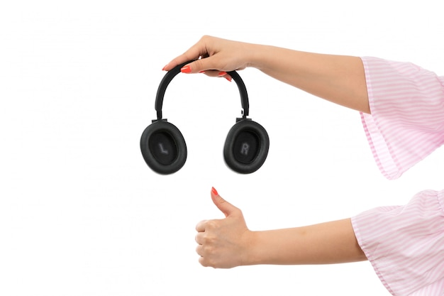 A front view female hand holding black earphones like sign on the white