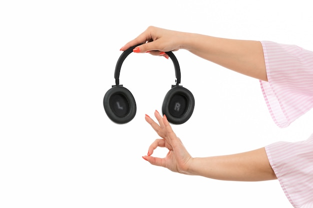 A front view female hand holding black earphones showing alright sign on the white