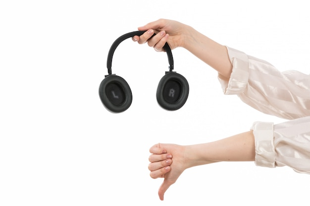 A front view female hand holding black earphones showing unlike sign on the white