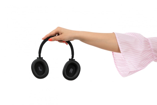 A front view female hand holding black earphones on the white