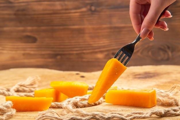 Vista frontale della mano femminile che tiene il formaggio sulla forcella