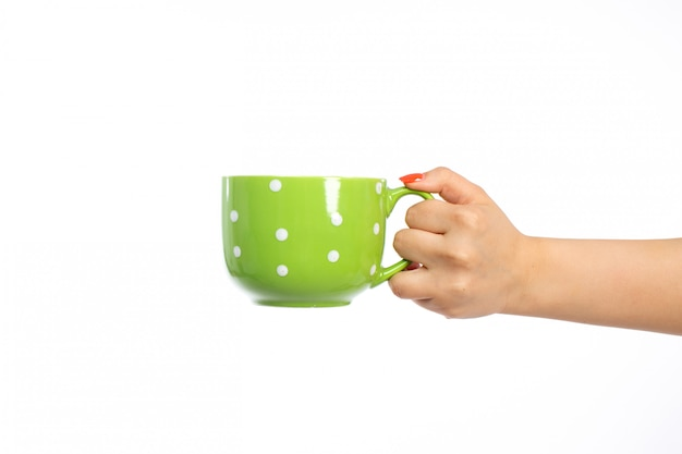 A front view female hand holding green cup on the white