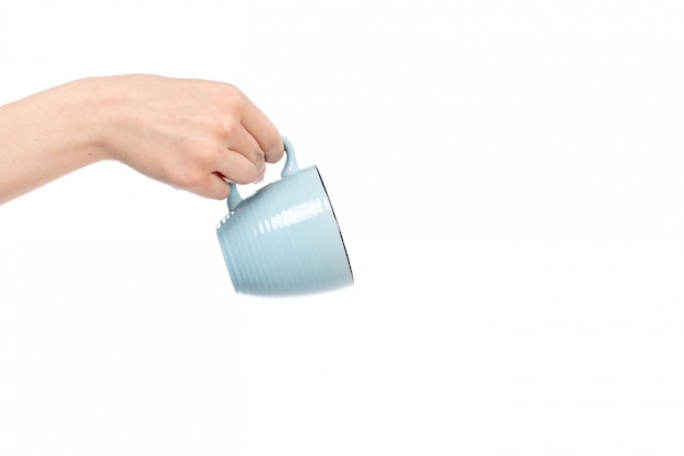 A front view female hand holding little blue cup hanging on the white