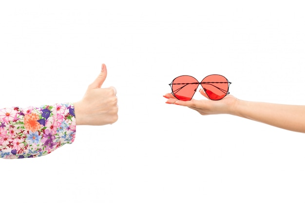 A front view female hand holding red sunglasses with other female showing awesome sign on the white