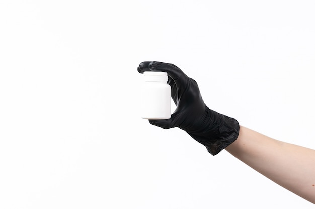 A front view female hand holding white tube in black gloves on white