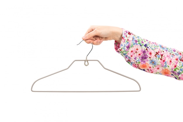 A front view female hand lady in colorful flower designed shirt holding silver hang on the white