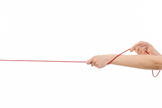 A front view female hand pulling up red rope on the white