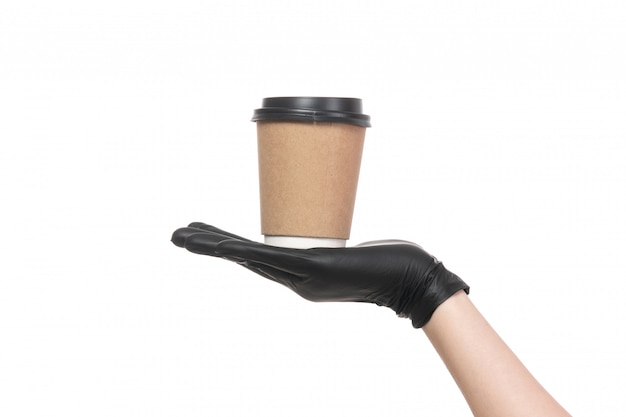 A front view female hand with black leather gloves holding cup of coffee on white