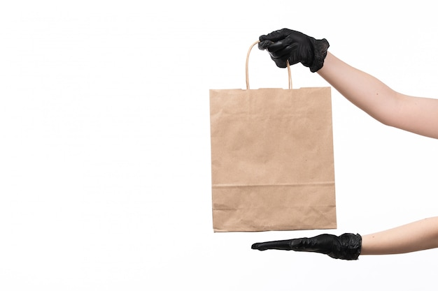 A front view female hands in black gloves holding brown paper package on