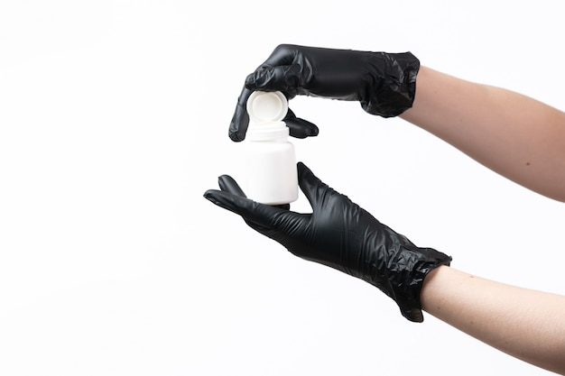 A front view female hands in black gloves holding white tube on white