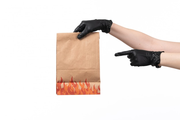 A front view female hands holding brown paper food packages on job