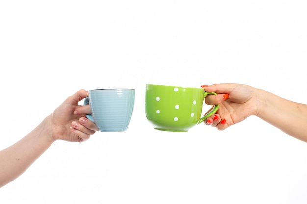 A front view female hands holding different colored cups on the white