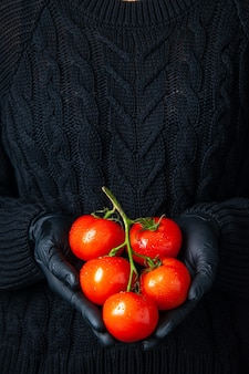 トマトの枝を保持している黒い手袋と正面図の女性の手