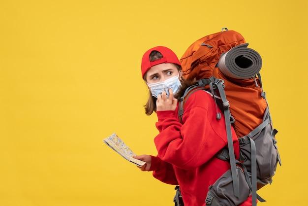 バックパックとマスク保持マップと正面図の女性ハイカー