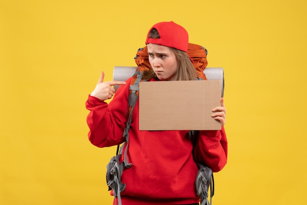 Autostoppista femminile di vista frontale che indica al cartone in bianco