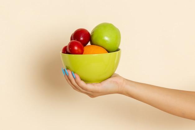 Вид спереди женщина держит тарелку с разными фруктами на бежевом