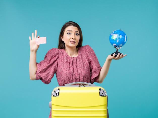 Вид спереди женщина в поездке, держащая маленький глобус и красную банковскую карту на синем фоне, путешествие, путешествие, отпуск, женщина, морское путешествие