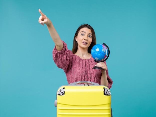 青い背景の旅旅行休暇航海女性海に小さな地球を保持している旅行の正面図の女性