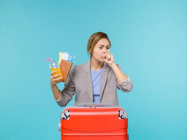 Вид спереди женщина в отпуске, держащая свежий напиток и билеты, кашляющая на синем фоне, морское путешествие, отпуск, путешествие, путешествие