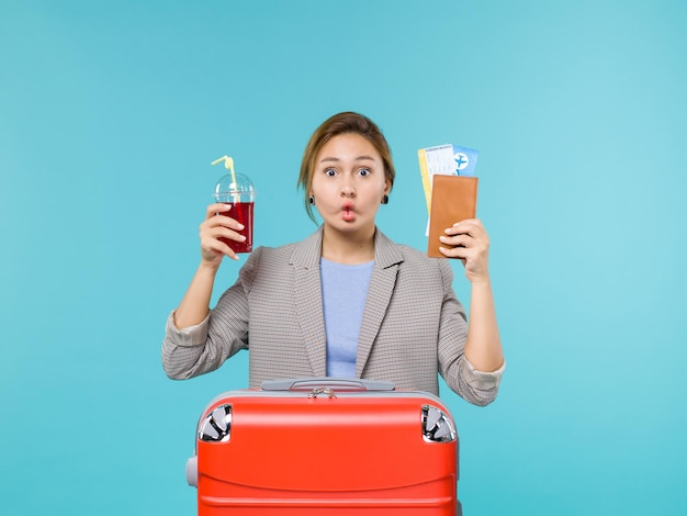 ジュースと青い背景の航海旅行飛行機休暇旅行のチケットを保持している休暇中の女性の正面図