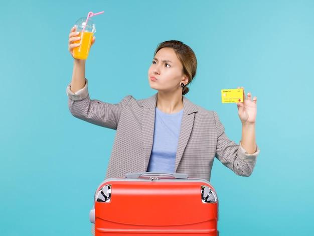 青い机の海の旅の休暇の飛行機の航海の旅でフレッシュジュースと銀行カードを保持している休暇中の女性の正面図