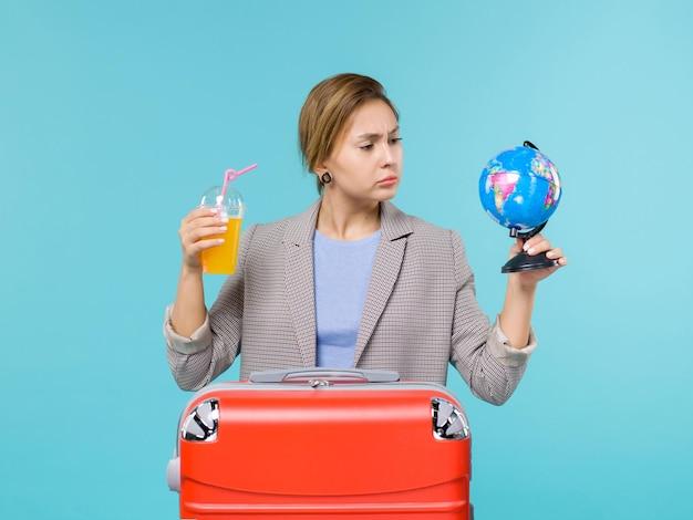 青い背景の海の休暇の航海の旅の旅でフレッシュジュースと地球儀を保持している休暇中の女性の正面図