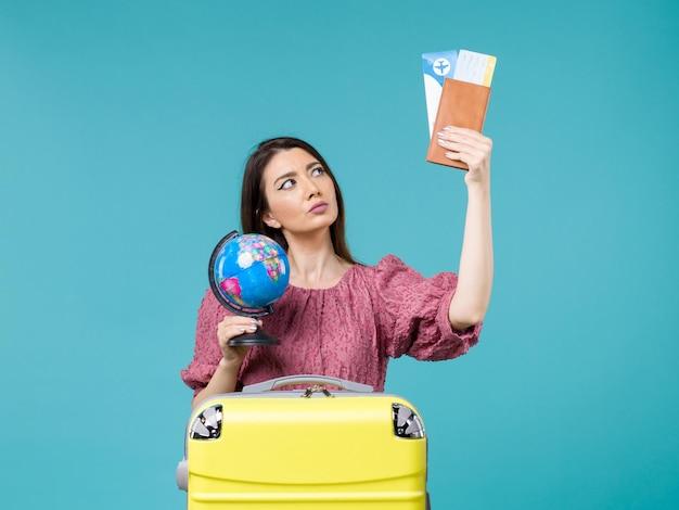 青い背景の海の休暇の女性の旅行の旅の夏に地球と飛行機のチケットを保持している休暇中の女性の正面図