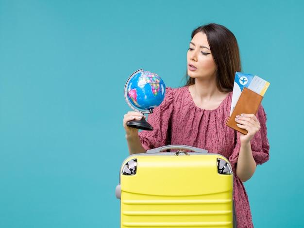 파란색 배경 바다 휴가 여자 여행 여행 여름에 글로브와 비행기 티켓을 들고 휴가에 전면보기 여성