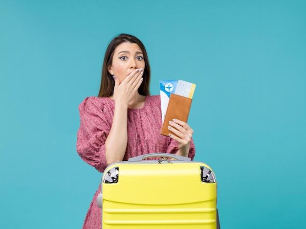 Вид спереди женщина в отпуске, держа билеты на голубом фоне, путешествие, поездка, отпуск, женщина, лето, море