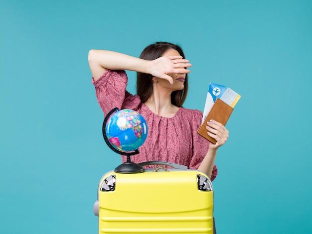 青い背景の海の旅の休暇の女性の航海の旅で彼女の財布とチケットを保持している休暇中の女性の正面図