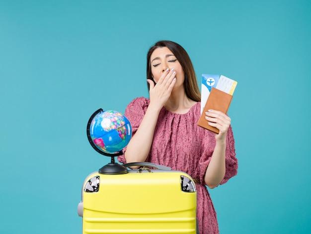 青い背景の海の旅の休暇の女性の旅の航海で彼女の財布とチケットあくびを保持している休暇中の女性の正面図