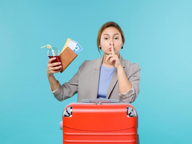 Вид спереди женщина в отпуске, держащая сок и билеты на синем фоне, рейс самолет, отпуск, путешествие, путешествие на море