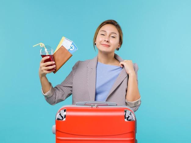 青い背景の航海休暇旅行旅行水上飛行機でジュースとチケットを保持している休暇中の女性の正面図