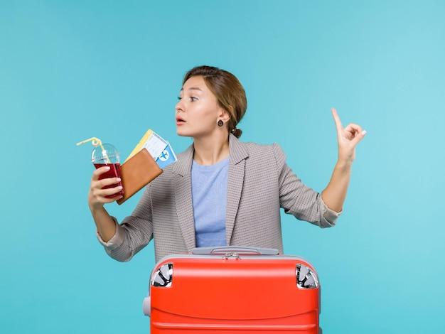 밝은 파란색 배경 항해 휴가 여행 여행 바다 비행기에 티켓과 주스를 들고 휴가에 전면보기 여성