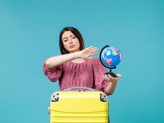 青い背景の海の休暇の旅夏の女性の旅行で小さな地球を保持している休暇中の女性の正面図