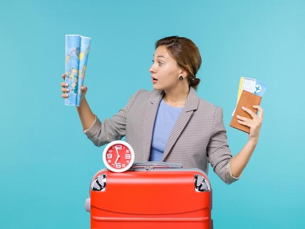 파란색 배경 비행기 여행 항해 여행 여행 휴가 바다에지도와 티켓을 들고 휴가에 전면보기 여성