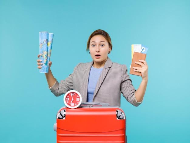 Вид спереди женщина в отпуске с картой и билетами на синем фоне, самолет, путешествие, путешествие, путешествие, отпуск, морское путешествие