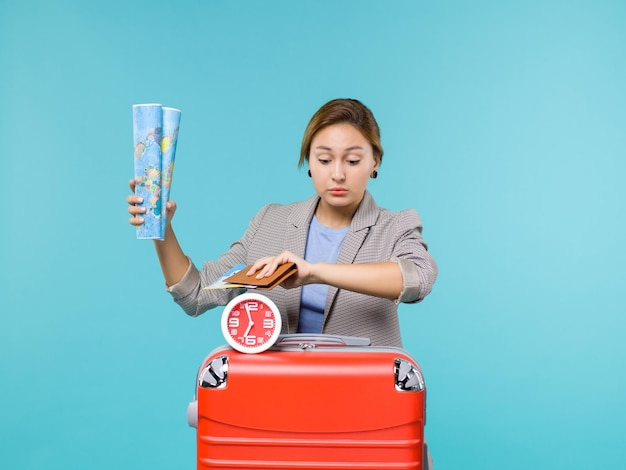 青い背景に地図とチケットを保持している休暇中の女性の正面図飛行機の航海の旅休暇海の旅旅行